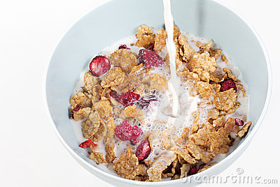 Milk being poured into bowl of muesli with fruits