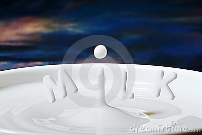 Milk drop or droplet dripping into a bowl full with letters added to make Milk