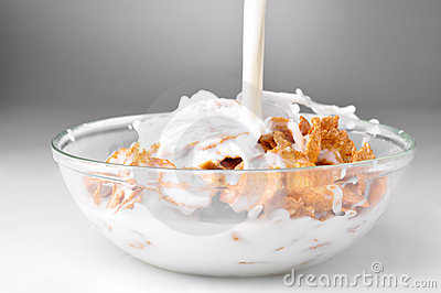 Milk flowing to the bowl with brown corn flakes