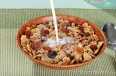 Milk pouring into bran and raisin cereal