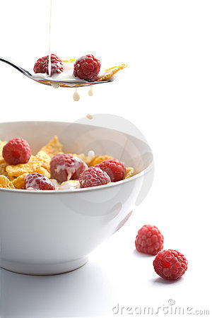 Milk pouring onto muesli with raspberry isolated