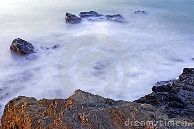 Milky early morning seas and rocks in Spain