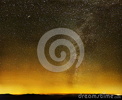 Milky way over black mountains and city lights