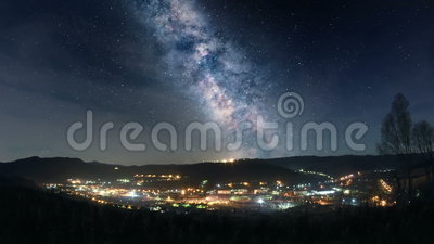 Milky Way over mountain town. Night time lapse of Milky Way over mountain town stock video