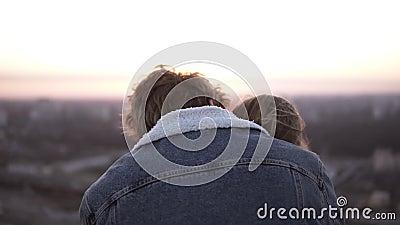 Millenial modieus paar - langharig meisje en blondy mens die zich op het winderige dak bevinden die met een mooie scène omhelzen stock footage