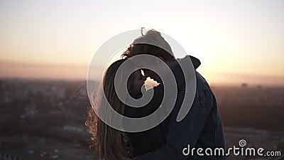 Millenial romantisch paar - langharig meisje en blondy mens die zich op het winderige dak bevinden die met een mooie scène omhelz stock videobeelden