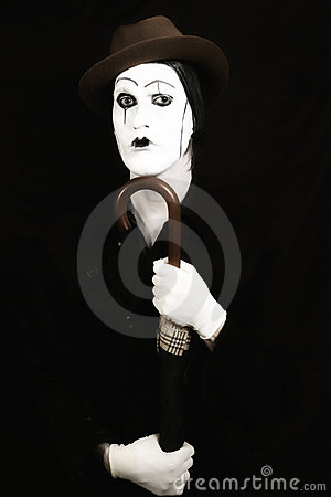 Mime in a hat holding an umbrella in his hand
