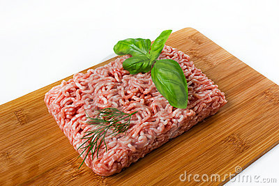 Minced meat with basil on a wooded cutting board