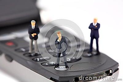 Mini businessmen on cellphone