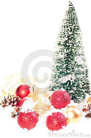 Mini Christmas tree with red, gold baubles on snow