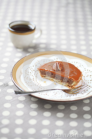 Mini Pecan Pie with Caramel Topping on a plate with a cup of coffee
