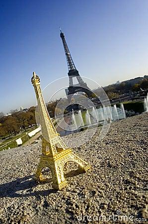 Miniatura de la torre Eiffel delante de la torre verdadera