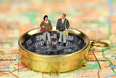 Miniature business travelers on a compass