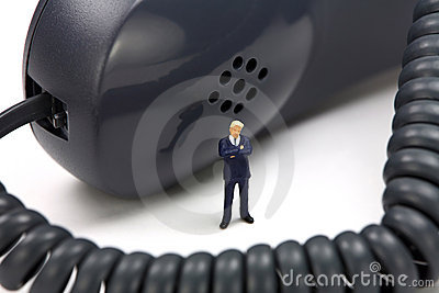 Miniature businessman stands in front of a phone