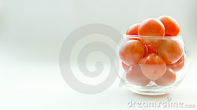 Miniature glass jar full of small tomatoes