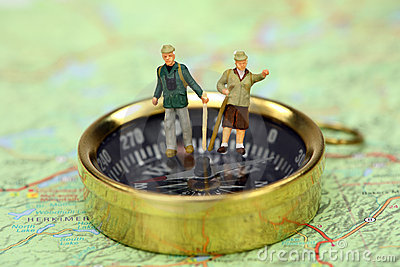 Miniature hikers standing on a compass.