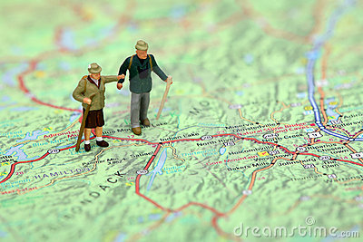 Miniature hikers standing on a map.