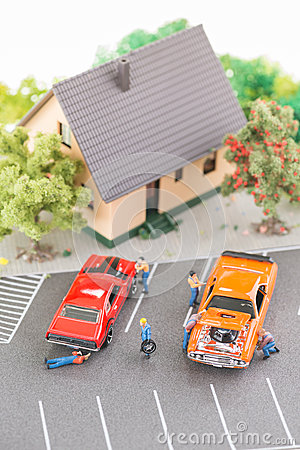 Miniature mechanics servicing and repairing cars top view