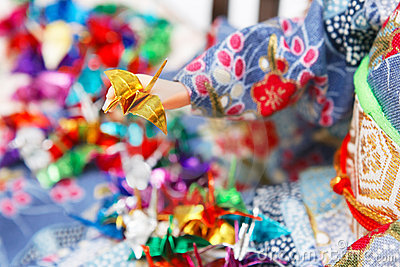 Miniature origami birds and a Japanese doll