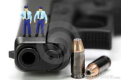 Miniature policemen standing on a gun.
