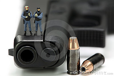 Miniature SWAT team standing on a gun.