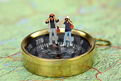 Miniature tourists taking pictures on a compass