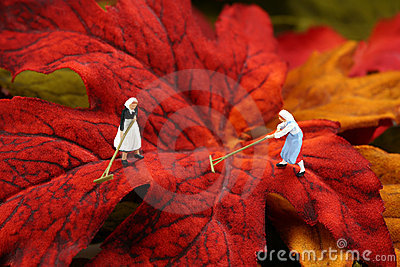Miniature women raking autumn leaves