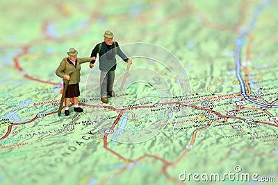 Miniatuur wandelaars die zich op een kaart bevinden.