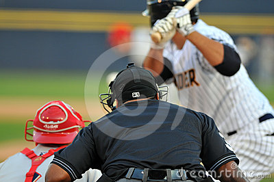 Minor league baseball - umpire watches the pitch Editorial Photography