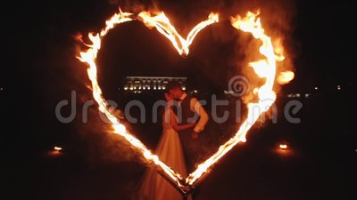 Minsk, Belarus - August 8, 2019: Bride and groom kissing in a flaming heart outdoor at night. Slow motion. Minsk, Belarus - August 8, 2019: Beautiful just stock video footage