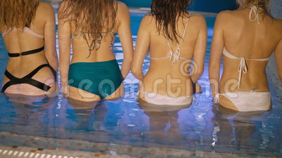 Mirada trasera del cuerpo del ` de las muchachas en el desgaste de la natación que presenta en el lavabo 4K metrajes