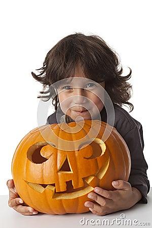 Mischievous Little boy with a Halloween pumpkin