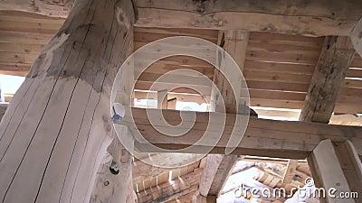 Mistrz polerowuje dziennik drewnianej ramy domu, stolarstwo Przytnij Widok na dno mężczyzny w białym mundurze i zdjęcie wideo
