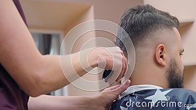 Mistrz w pracy w salonie fryzjerskim, bliski strzał Stylista siekający włosy na pinezce samców z pinezką Zarejestrowane w zdjęcie wideo