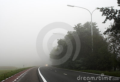 Misty road with car headlights far away