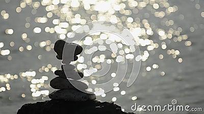 Mit Ziegeln gedeckte Felsen silhouettieren mit Sonnenscheinen im Wasser hinten stock footage