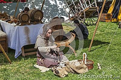 Mittelalterliche junge Frauen-spinnende Wolle Redaktionelles Stockfoto
