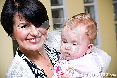 Mittlere gealterte Mama mit Schätzchen