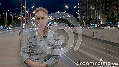 Mittlere gealterte Person mit Wasser sitzt auf Steingeländer nachts stock footage