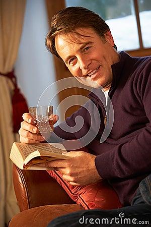 Mittlerer gealterter Mann mit Buch-trinkendem Whisky