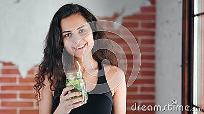 Mittleres Nahporträt von schöner gemischter Athletin, die gesundes Getränk trinkt stock video