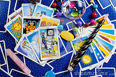 Mixed blue tarot cards with a magic ball and wand.
