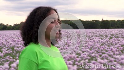 Mixed race African American girl teenager female young woman walking in field of pink poppy flowers drinking a bottle of water stock footage