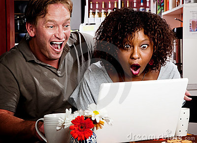 Mixed race couple in coffee house with laptop comp