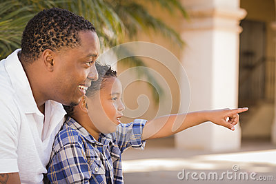 Mixed Race Father and Son Pointing in the Park