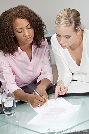 Mixed Race Young Businesswomen Signing A Contract