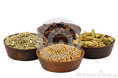 Mixed spices in small wooden bowls isolated on white