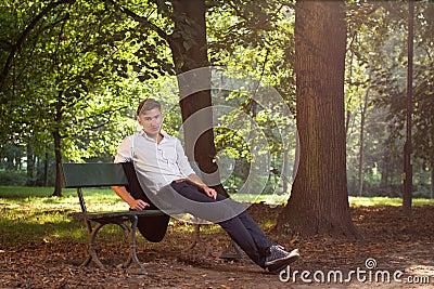 Männliches vorbildliches Sitzen auf einer Bank