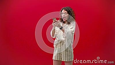 A moça curly joga em um iPhone 11pro em uma mão sobre um fundo vermelho video estoque