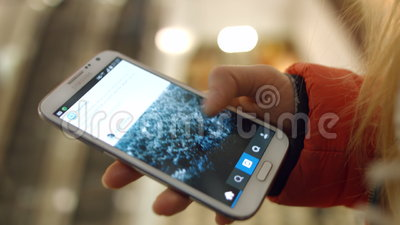 A moça olha o close up das fotos das aplicações e do olhar do telefone celular 4K 30fps ProRes video estoque
